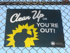 Schild mit Text: »Clean Up or You're Out!«